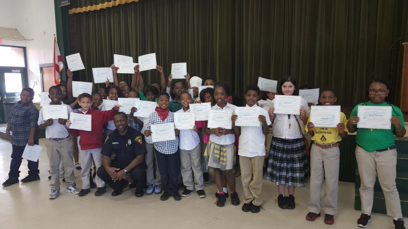 Leinkauf Elementary students hold up certificates after completing MPD's G.R.E.A.T. program.